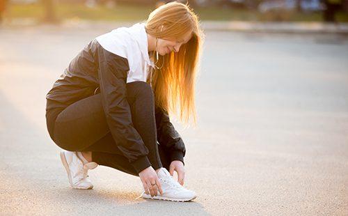Спортивная девушка завязывает шнурки
