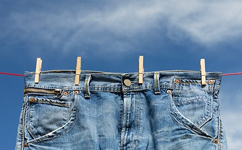 Джинсовые брюки висят на верёвке