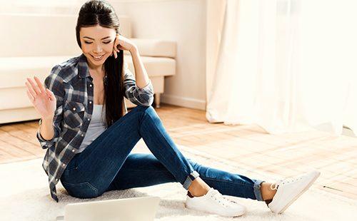 Девушка в белых кроссовках сидит на полу