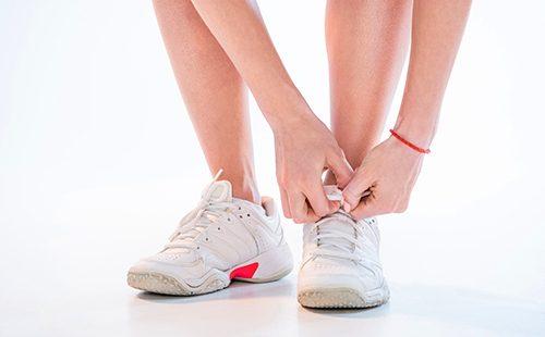 Руки шнуруют спортивную обувь