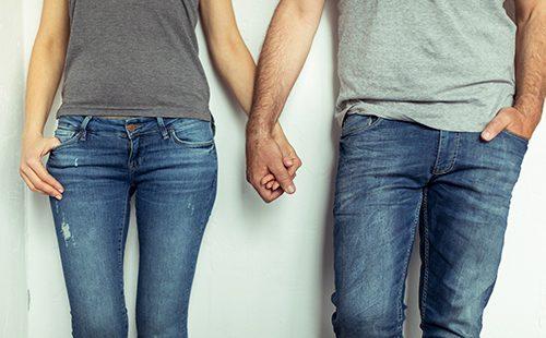 Парень и девушка в джинсах держатся за руки