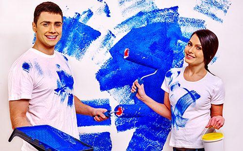 Счастливая пара красит стену