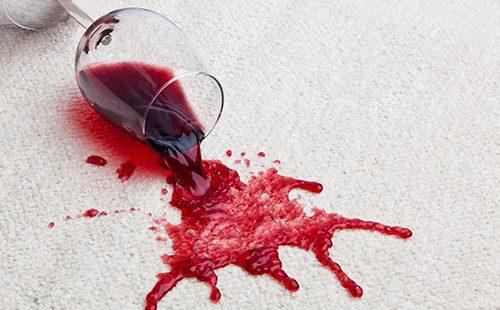 Рубиновый напиток бесцельно разлит по белому ковру