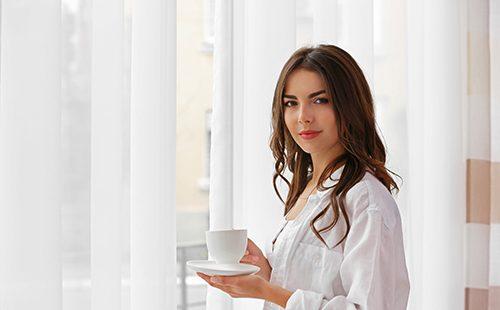 Девушка у окна с белейшими занавесками