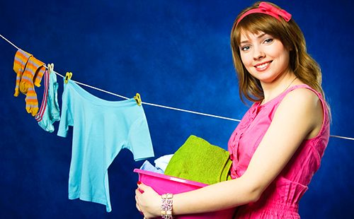 Молодая домохозяйка развешивает бельё