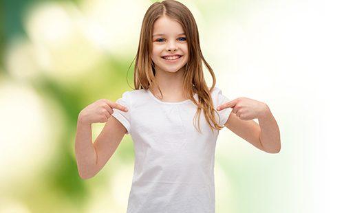 Девочка с улыбкой показывает на свою одежду