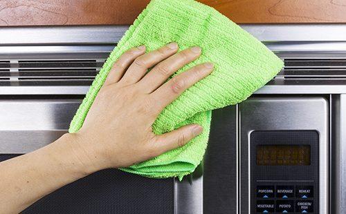 Рука с зелёной салфеткой протирает печь снаружи