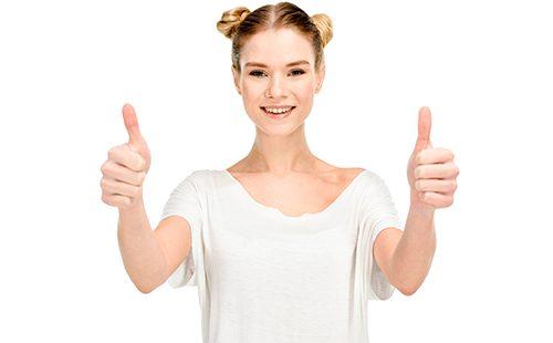 Радостная девушка в белой футболке показывает большие пальцы
