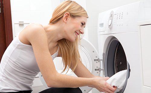 Молодая женщина у стиральной машины