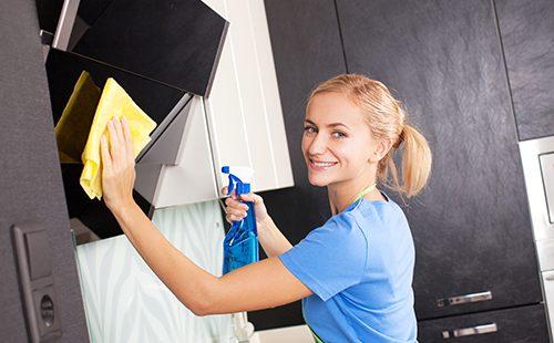 Женщина протирает кухонную мебель