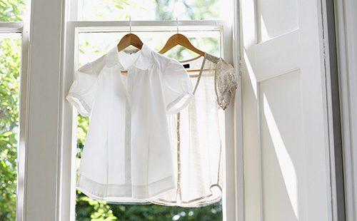 Белые блузки висят у открытого окна