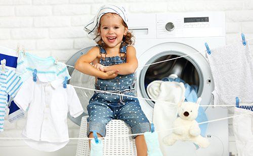 Весёлая маленькая девочка играет в прачку