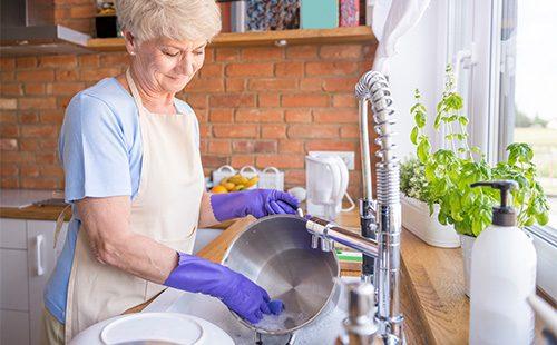 Женщина моет кастрюля