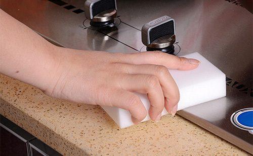 Женщина моет плиту