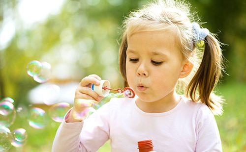 Маленькая девочка играет с мыльными пузырями