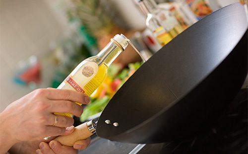 Наливает масло в сковороду вок