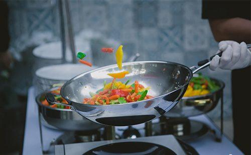 В сковороде вок жарятся овощи