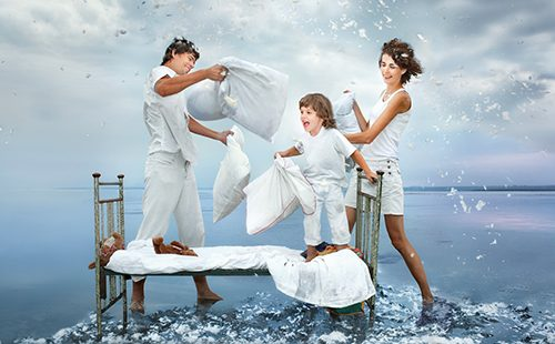 Молодая семья шутливо дерётся подушками на фоне моря
