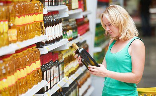 Женщина выбирает оливковое масло в магазине