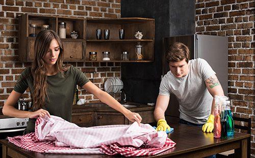 Молодая пара убирается на кухне