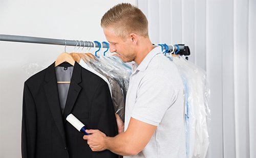 Мужчина чистит пальто