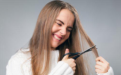 Девушка с яростью режет прядь своих длинных волос