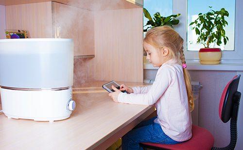 Девочка с планшетом сидит возле увлажнителя