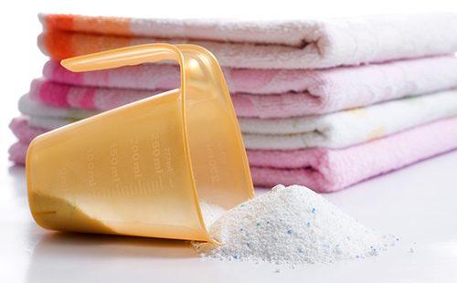 Мерная чашка перед стопкой полотенец