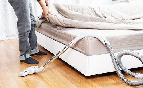Мужчина пылесосит постель
