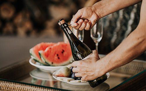 Открывает бутылку шампанского