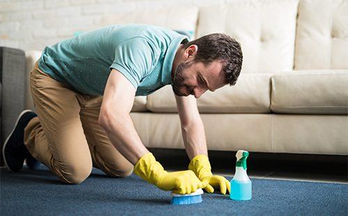 Мужчина чистит ковер